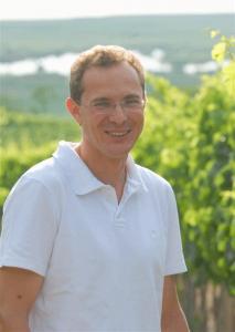 Winzer Franz Sommer im Weingarten mit Blick auf Neusiedler See